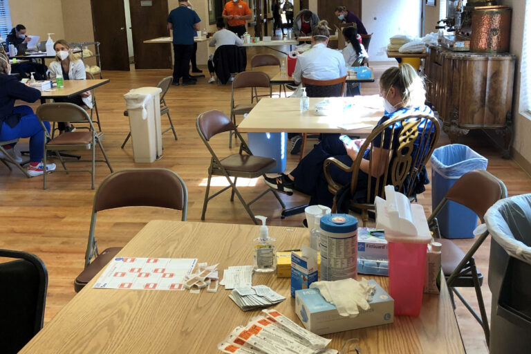 Healthcare workers preparing tables to vaccinate residents.