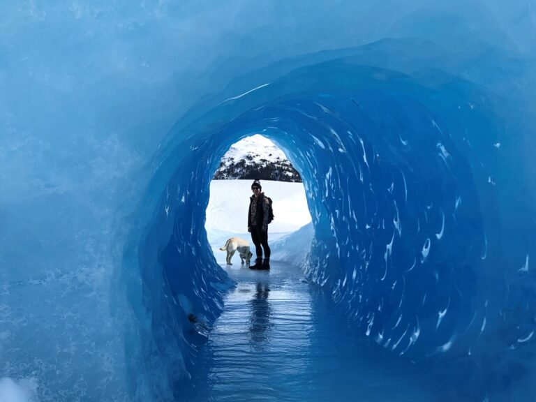 Heidi Voss standing at the end of an ice tunnel