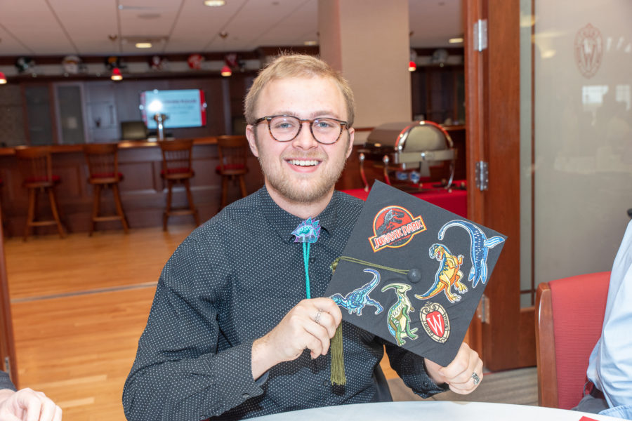 A student holding up his graduation hat at the PharmTox graduation breakfast.